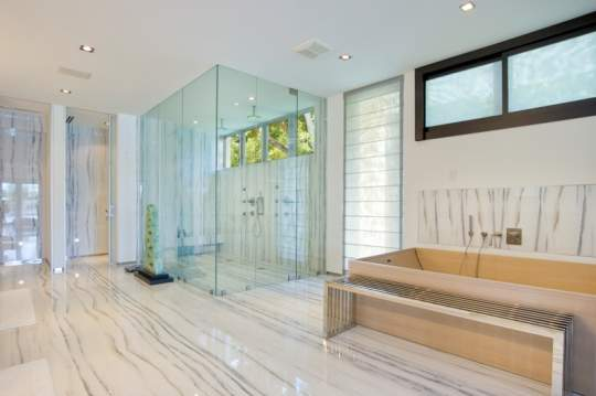 Spacious Bathroom With Glass Shower Doors And Marble Floors